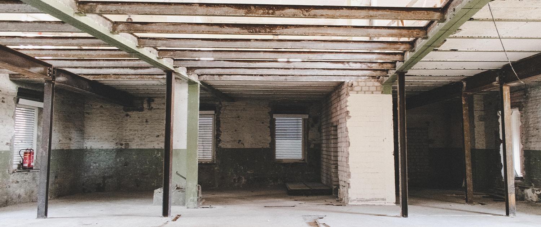 Ein großer leerer Raum mitten im Umbau, die entblößten Stahlbalken der Decke sind leicht rostig, einige Wände fehlen und es stehen nur Stahlsäulen, bei der noch vorhanden Wand erkennt man unterschiedliche Lagen von Farbe und Tapete.
