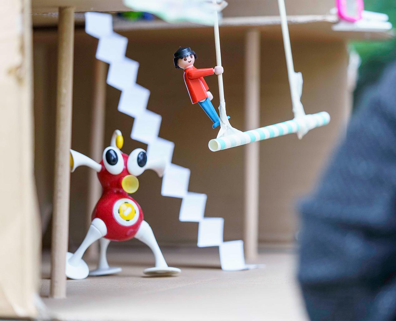 In einer Miniquartiershalle aus Pappe ist ein Strohhhalm an zwei Schnüren an der Decke befestigt, darauf schaukelt eine Legofigur. Eine rote Alienfigur mit drei Beinen steht in in der Halle.