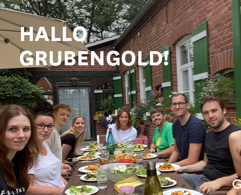 Das Team von Grubengold sitzt an einer langen Tafel voller Essen und Trinken. Im Hintergrund ein altes Backsteinhaus und Sonnenschirm.