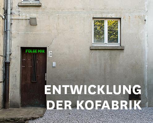 """Rechts unten steht in weißen Großbuchstaben """"Entwicklung der KoFabrik"""".Das Bild zeigt eine alte graue Wand. Rechts ist ein Fenster, links eine dunkle Holztür mit aufgeklebter Schrift aus neongrünem Klebeband: """"FOLGE MIR""""."""