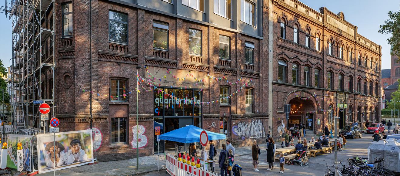Die KoFabrik, ein rotes Backsteinhaus mit alter Fassade und einer modernen grauen Aufstockung auf dem vorderen Teil. Auf der Straße davor stehen viele Menschen, alles ist mitWimpeln gescmückt.